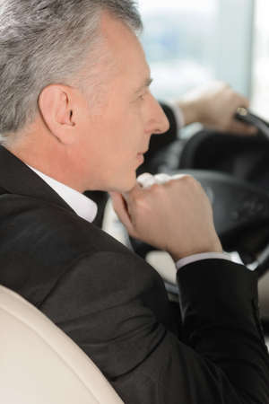 stitting: I have made a right choise  Senior businessman thinking about a choise he made touching his chin with the hand
