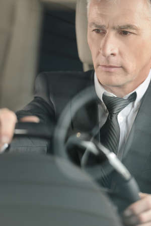 stitting: Senior businessmen driving a car  Confident senior businessman driving a car