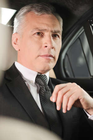 stitting: Business trip  Confident senior businessman sitting at the back seat of the car Stock Photo