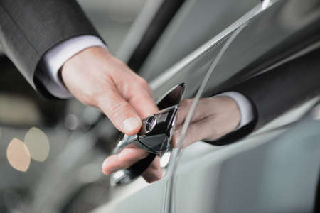 opening door: Hand on the car handle  Businessman holding his hand on the casr handle Stock Photo