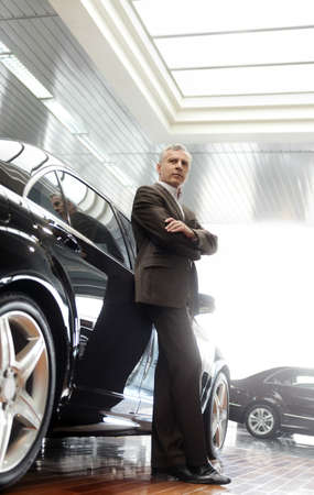 car dealership: This car is perfect for me  Confident senior businessman leaning on his new car he choosed at the dealership