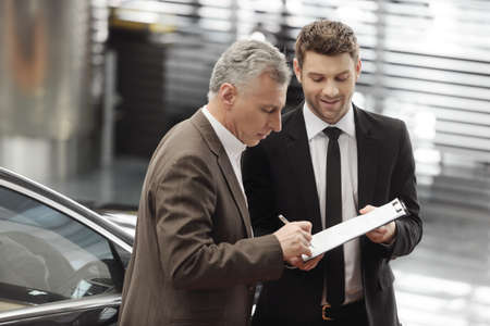 needed: Please, sign hear  Handsome young car salesman helping his client to sign all the documents needed Stock Photo
