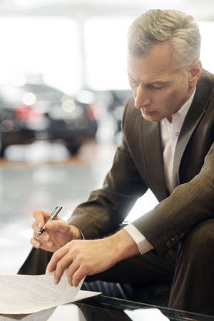 only men: Signing a contract  Confident senior businessman signing a contract at the dealership Stock Photo