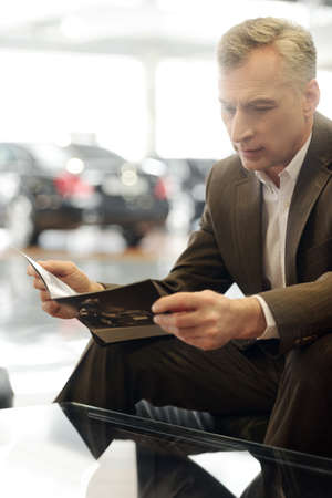 reading magazine: Now I see the advantages  Confident senior businessman reading a car magazine