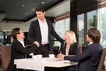 greet: Handsome business man greeting group of people. Sitting at restaurant drinking coffee Stock Photo
