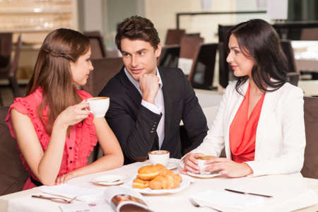 Man with two beautiful women sitting at the restaurant. Talking and drinking coffee photo