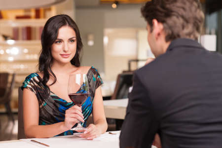 ワイングラスで彼女の恋人を見ている美しい女性を誘惑します。ロマンチックな話を持っています。