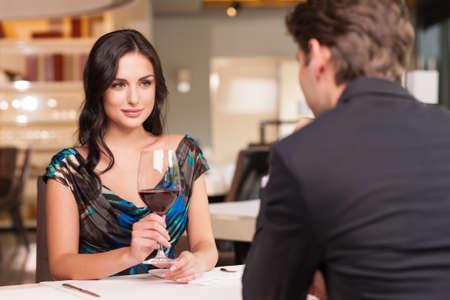 romântico: Seduzindo mulher bonita olhando para seu amante com um copo de vinho. Tendo conversa rom