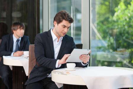 negocios comida: Atractivo hombre de negocios comprobando su horario con el touchpad. Mientras que el consumo de caf� en la cafeter�a