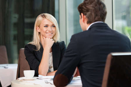lunch meeting: Smiling attractive businesswoman and man having discussion. While drinking coffee at lunch break