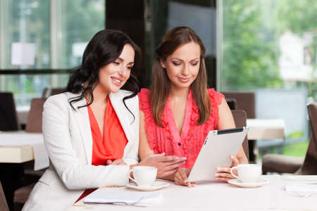 Two female friends looking at touchpad. Smiling and looking happy photo