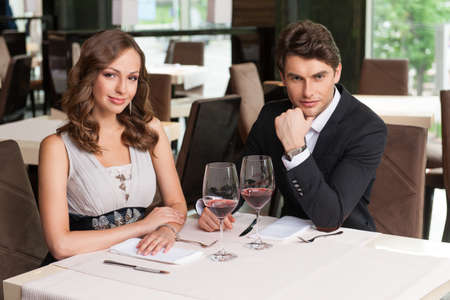 Beautiful couple sitting at the restaurant. Waiting for food, looking at camera photo