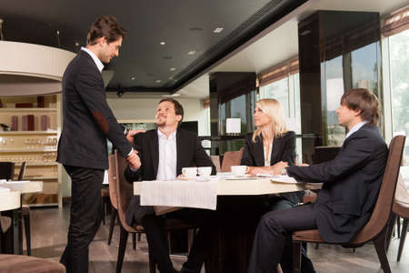 impressions: Group of well dressed business people greeting  handsome businessman. Looking and shaking hands at restaurant