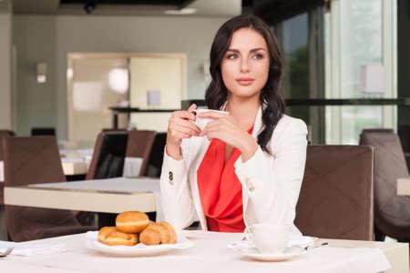 aside: Beautiful dark hair woman sitting at the restaurant. Looking away drinking coffee