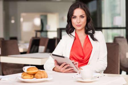 Attraktive Frau, die Kamera während der Sitzung im Restaurant. Mit ipad