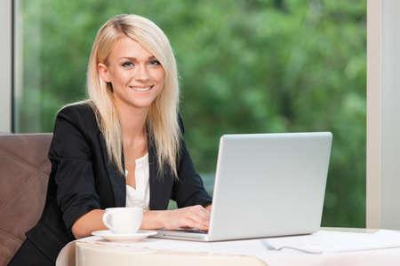 Lächelnde schöne blonde Geschäftsfrau mit Laptop. Trinken Kaffee im Restaurant