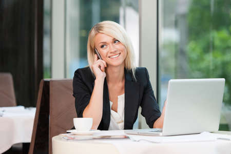 Beautiful blond businesswoman talking by phone. While sitting at café with laptop