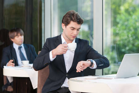 Busy businessman is looking at watch. While drinking coffee photo