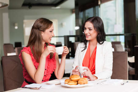 Two girlfriends meet at café for breakfast. Talking and gossiping Stock Photo