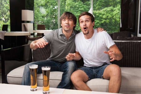 Two male football fans cheering football team. Drinking bear in pub, green trees on background photo