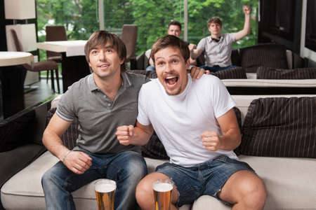 football party: Group of fans cheering football team in beer pub. Having happy emotions on face