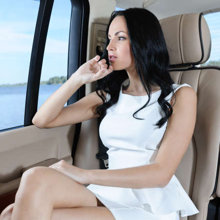 A gorgeous young Caucasian woman in a white dress looking through the car window photo