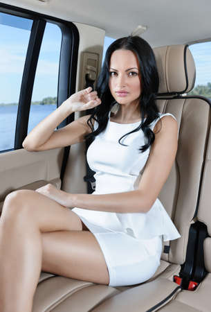 legs crossed at knee: A gorgeous young Caucasian woman in a white dress sitting on the back seat of her car looking at camera Stock Photo