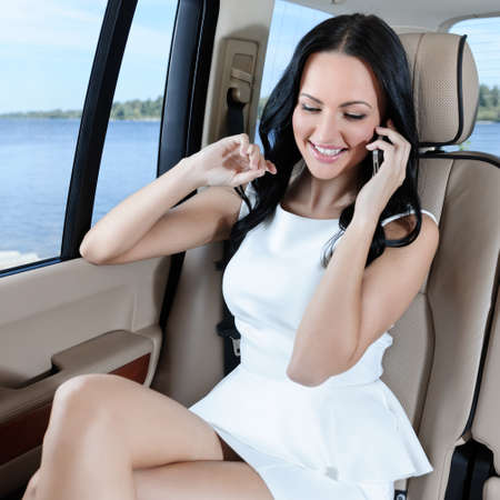 legs crossed at knee: An attractive young Caucasian woman in a white dress talking on the phone during the car trip