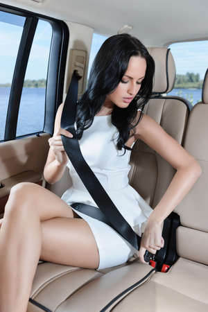 Eine attraktive junge kaukasischen Frau in einem weißen Kleid Befestigung ihre Sicherheitsgurt vor der Autofahrt