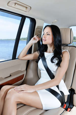 An attractive young Caucasian woman in a white dress looking through the window sitting on the back seat of her car photo