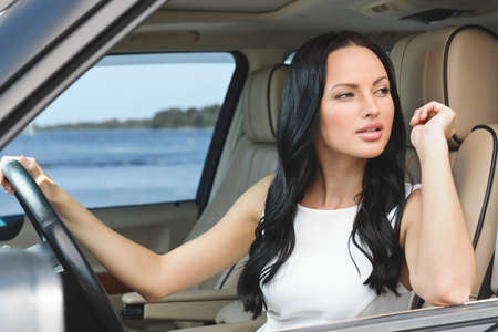 woman driving car: An attractive young Caucasian woman looking away into the distance through her opened car window