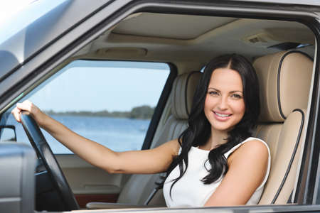 An attractive young Caucasian woman looking at the camera from the front seat of the car photo