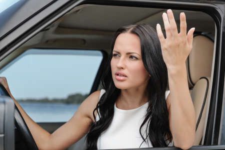 An attractive young Caucasian woman arguing with someone from the front seat of the car photo