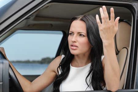 mujer enojada: Una mujer joven de raza blanca atractiva discutiendo con alguien desde el asiento delantero del coche