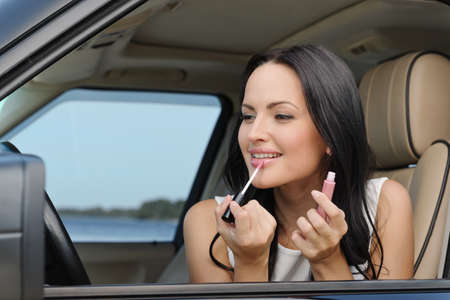 A beautiful young Caucasian woman doing make-up on the front seat of the car photo