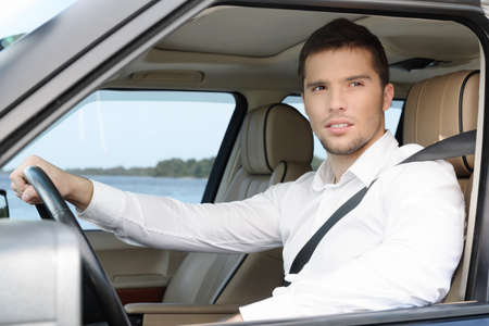 Handsome young man in white shirt looking through the window of his car holding the right hand on the wheel photo