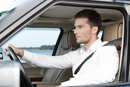Handsome young man in white shirt driving the car holding the right hand on the wheel photo
