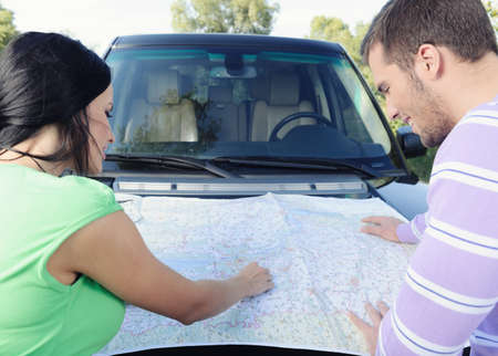 Beautiful young couple looking at the map pointing the places on it standing in front of the car photo