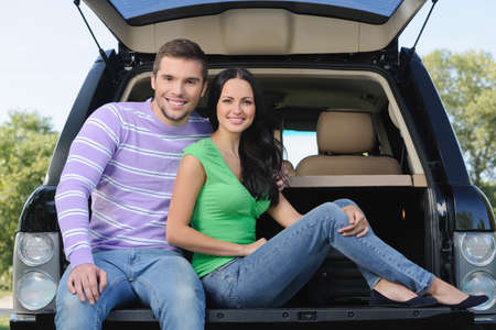 Beautiful young couple seating on the luggage boot of the car smiling on camera photo