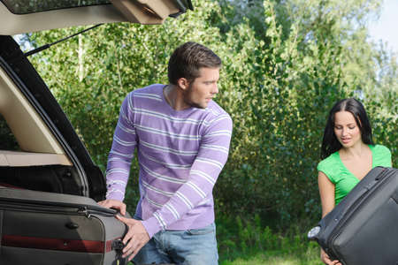 open car door: An attractive young couple packing their stuff into the trunk