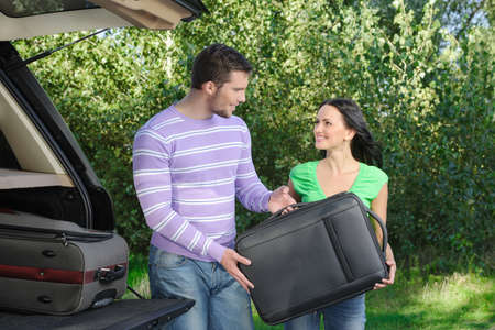 An attractive young couple packing the luggage into the trunk photo