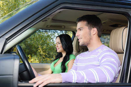 man front view: Attractive young couple enjoying a long drive in their new car