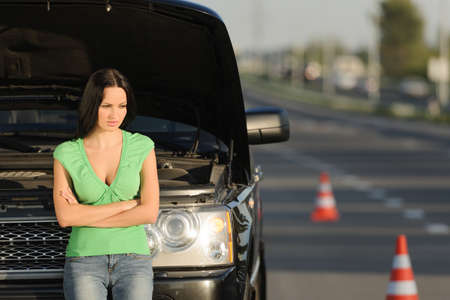 An attractive young Caucasian woman standing in front of her broken car with the hood open photo