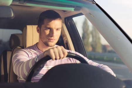 Gut aussehender junger Mann, der ein Auto hält die rechte Hand auf dem Rad