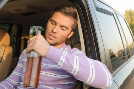 drunk driving: Young man holding a bottle of wine in his hand and driving a car