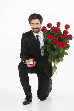marry me: Will you marry me? Young man in full suit standing on one knee and making a proposal while isolated on white background