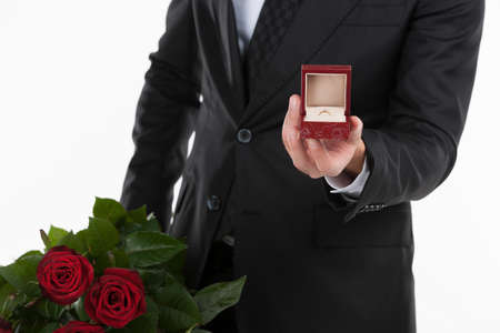 outstretching: Marry me! Cropped image of men in suit holding an open box with engagement ring and a bunch of roses while inside standing against white background Stock Photo