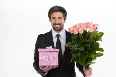 Men with gift box and flowers. Cheerful young men in formalwear holding a gift box and bunch of flowers in his hands while standing against white background photo