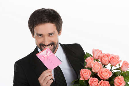 Men with greeting card and flowers. Portrait of cheerful young men in formalwear holding a greeting card and bunch of flowers in his hands while standing against white background photo