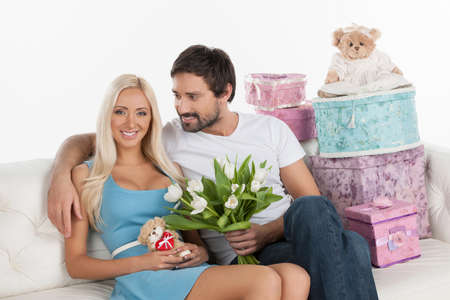 Young loving couple. Beautiful young couple holding flowers and teddy bear while sitting on the couch with gift boxes on it photo